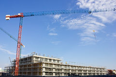 Highrise Construction. Concrete Highrise Construction site and Tower Cranes Royalty Free Stock Images