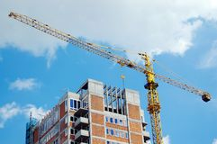 Highrise construction. Raw state residential highrise and jib crane over cloudy sky Royalty Free Stock Images