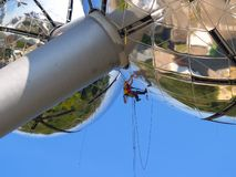 Highrise construction worker. High-rise construction worker suspended on steel cables working on a modern and daring spherical steel building Stock Image