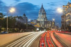 Highrise tower at night with car light trails. Skyscrapper cityscape at night. Heavy traffic, car light trails. Moscow. Mayakovskaya Stock Photo