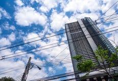 Highrisebyggnad och det invecklat över kraftledning royaltyfri fotografi