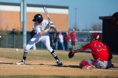 Highschool Baseballschagmann nimmt eine Neigung an den Knien Stockfotografie