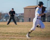 Highschool Baseballschiedsrichter passt den Läufer auf Stockfotografie