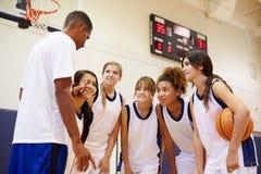 Highschool Basketball-Team Having Team Talk With-Trainer stockfotografie