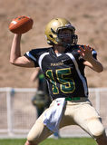 Highschool Fußball-Quarterback, der den Ball führt Stockbild