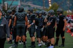 Highschool Fußball-Spieler, die Spiel-Strategie besprechen stockfotografie