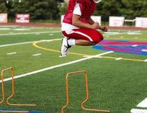 Highschool Fußballspieler, der über Hürden springt lizenzfreie stockfotografie