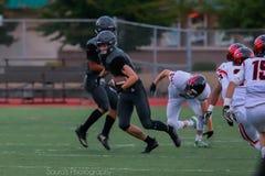 Highschool Fußballspieler, der mit Ball läuft stockfotos