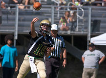Highschool Fußball-Quarterback, der den Ball führt Lizenzfreies Stockbild