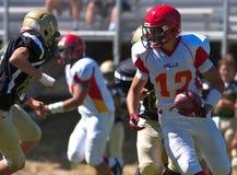 Highschool Fußball-Spieler, der mit dem Ball läuft Stockfotos