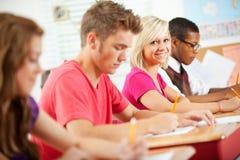Highschool: Lächelndes Mädchen während des Klassen-Quiz Stockfotos