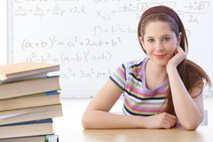 Highschool student smiling front of whiteboard. Highschool student sitting in classroom front of whiteboard, smiling royalty free stock image