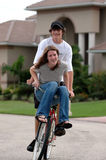 Highschool sweethearts. A teenage couple riding a bike together with the girl on the handle bars stock image