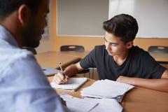 Highschool Tutor Giving Male Student eins bis eins Unterricht am Schreibtisch lizenzfreie stockfotos