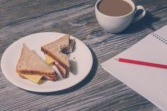 Hight学习企业杂文的学校教育写大学生概念 中断工作 在w的被咬住的火腿和乳酪三明治 免版税库存照片