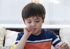 Free Hight Key Light Of Cute Boy Biting Finger And Looking Down, Happy Kid Putting Fingers In His Mouth With Curious Face While Stock Images - 184597324