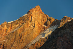 Hight scarlet mountain peak in sunset rays Stock Images