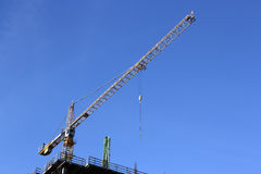 Hight tower crane. A crane sitting high on top of a construction site is being used to lift materials onto the top floor from the ground or around the site Stock Images
