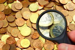 Highther valueted coins by magnifier. Coins zoomed from cents to euros by magnifier royalty free stock images