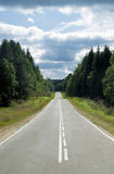 Highway. In the forest in front of cloudy sky Royalty Free Stock Photos