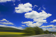 Highway 2. Landscape and highway with motion blur and blue cloudy sky Royalty Free Stock Photography