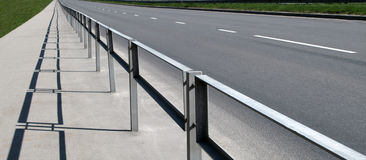 Highway. With a pedestrian path in solar spring day Royalty Free Stock Photography