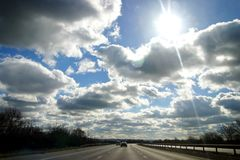 Highway. Sunny day with fluffy clouds seen from a car on the motorway Stock Photography