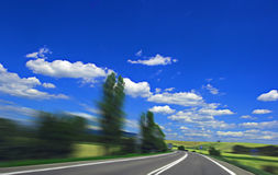 Highway. Asphalt highway with motion blur and blue cloudy sky Stock Photography