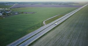 Highway aerial panorama with field and village. Drone 4K panning tilt shot. Logistics transportation network industry. Freeway aerial panorama with field and stock video footage
