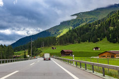 Highway along green fields and mountains in Switzerland. Royalty Free Stock Image