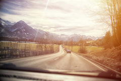 Highway in the Alps. view from inside car, sunset or sunrise Stock Photos
