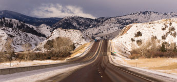 Highway Approaches South Fork River Crossing Utah. Winter scene with tucks coming and going on icy roads in Utah Royalty Free Stock Images