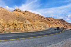 Highway in Arava desert. Highway along mountains of Arava desert under beautiful cloudy sky in Israel Royalty Free Stock Photography