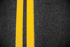 Highway Asphalt surface with two yellow lines. Royalty Free Stock Photo