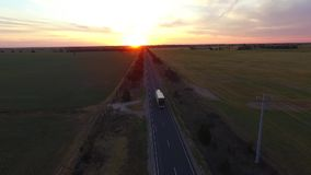Truck on rural road at sunset. Aerial view of truck driving on rural road at sunset stock video footage