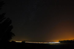 Highway on a background of bright stars of the night sky and the Royalty Free Stock Image