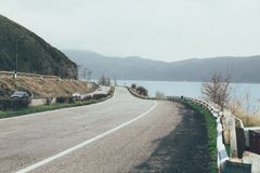 Highway with a background of lake and mountains royalty free stock photos