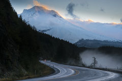 Highway beneath snowy mountain at sunrise Stock Image