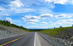 Highway ,in the blue sky. Alaska Royalty Free Stock Photography