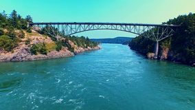Highway bridge by oceanfront on a sunny day. Revealing aerial view of a bridge crossing an ocean bay on a bright, windy and sunny summer day stock video