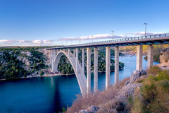 Highway bridge over Krka river, town of Skradin in background. Highway bridge over the Krka river, town of Skradin in background, the bridge is painted in sunset Royalty Free Stock Photo