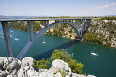 Highway bridge over a river. A highway bridge crossing river Krka near city Skradin in Croatia. Sailboats sailing on the river Stock Photography
