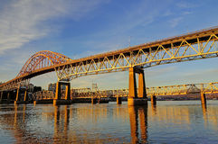 Highway bridge and railroad bridge are bathed in the golden rays of the sunset Stock Photos