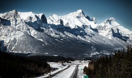 A highway in canadian rockies .Canmore , Alberta. A highway in winter in canadian rockies , Snow covered mountains in background Deep blue sky royalty free stock photography