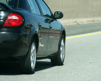 Highway Car. A black car speeding on the highway Royalty Free Stock Photo