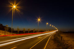 Highway car lights. A long exposure to capture the motion of the traffic on a busy highway or road. Street lamps light thw way Stock Images