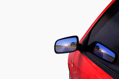 Highway in car mirror. Red car isolated on white background with highway and oncoming traffic lights reflected in rear view wing mirror Royalty Free Stock Image