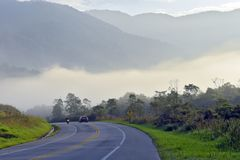 Highway with car, motorcycle and fog. Highway with car and motorcycle. In the background, fog, hills and trees. Rio Santos Road, Sao Paulo, Brazil royalty free stock photography