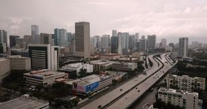 The highway carries commuters along side tall buildings in Miami Florida stock video