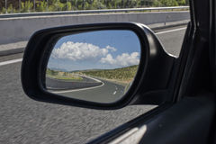Highway clouds. Driving on a motorway while looking at the cloudy sky through the mirror Stock Photo